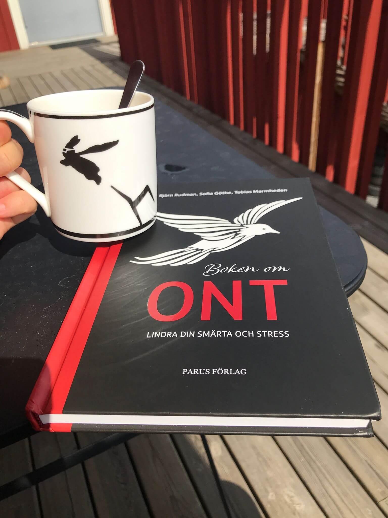 Dricker kaffe och läser Boken om Ont